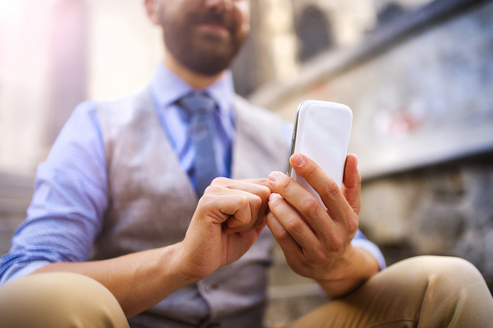 Detail of handsome hipster modern businessman using smart phone in the city