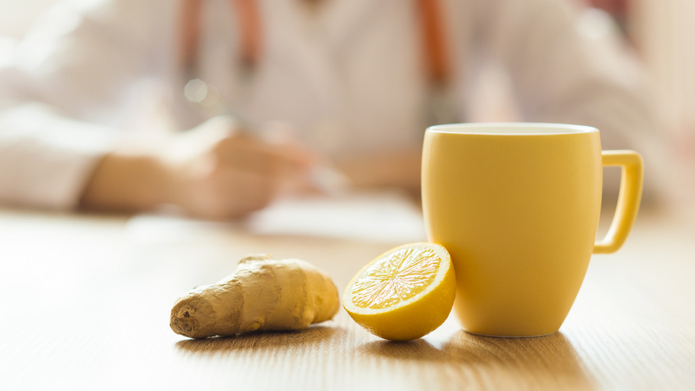 Detail of honey, lemon and cup of tea with doctor woman in background