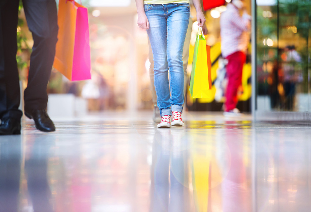Detail of legs of young couple with bags in shopping mall