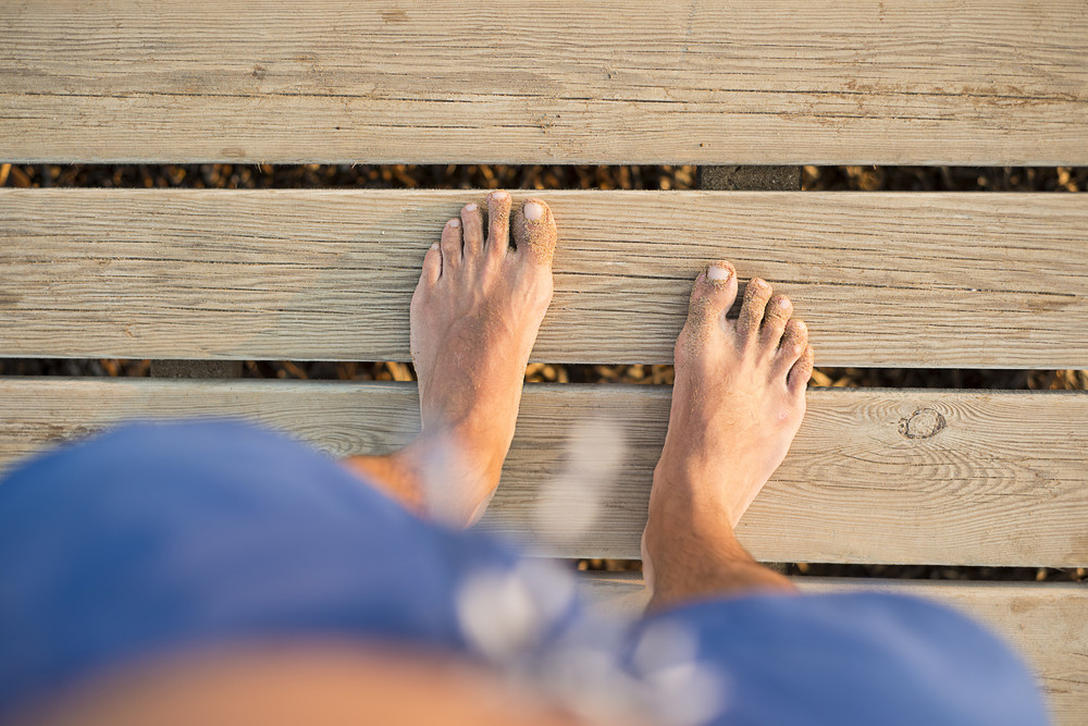Detail of male barefoot feet on sunny wooden pier