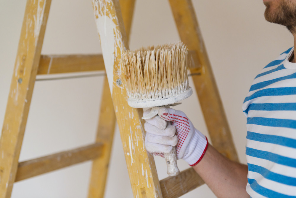 Detail of man painting the walls of new home with paintbrush
