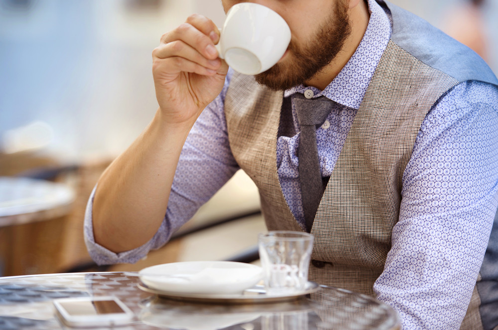 Detail of modern hipster businessman drinking espresso coffee in the city cafe during lunch time