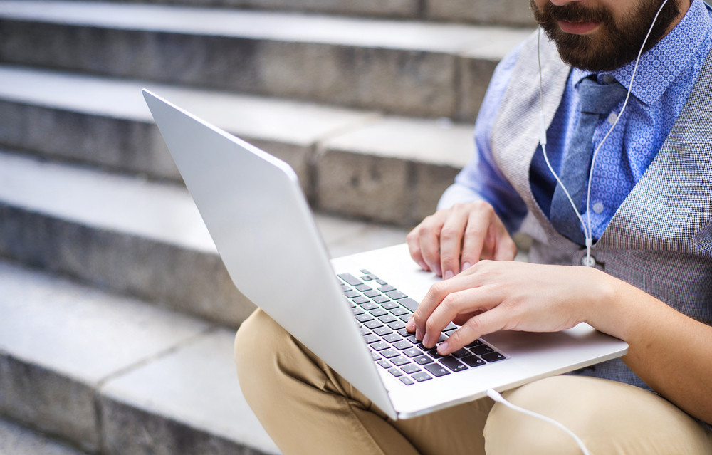 Detail of modern hipster businessman sitting on the stairs and using laptop