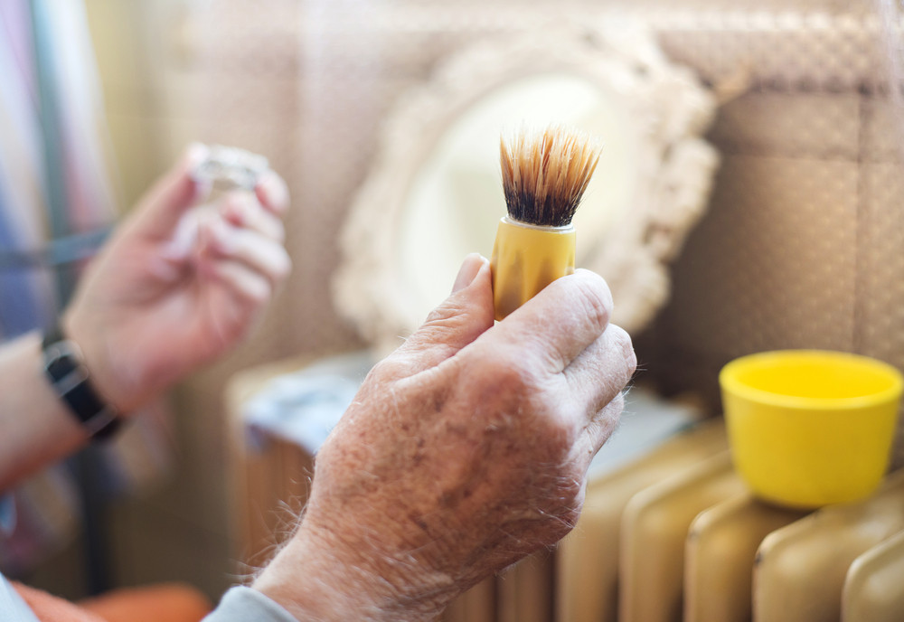 Detail of seniors man hand shaving his beard in bathroom in front of the mirror