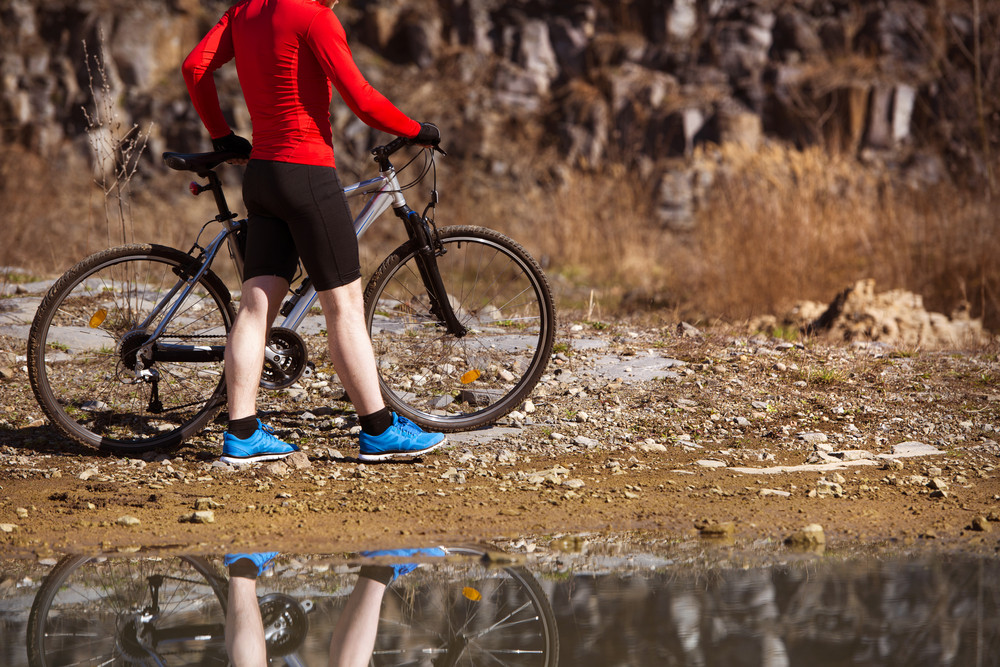 Detail of standing cyclist man reflecting in water puddle