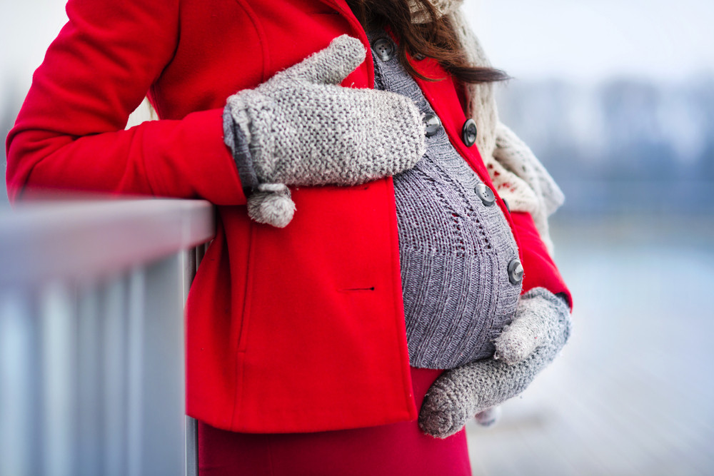 Detail of unrecognizable pregnant woman's belly in winter