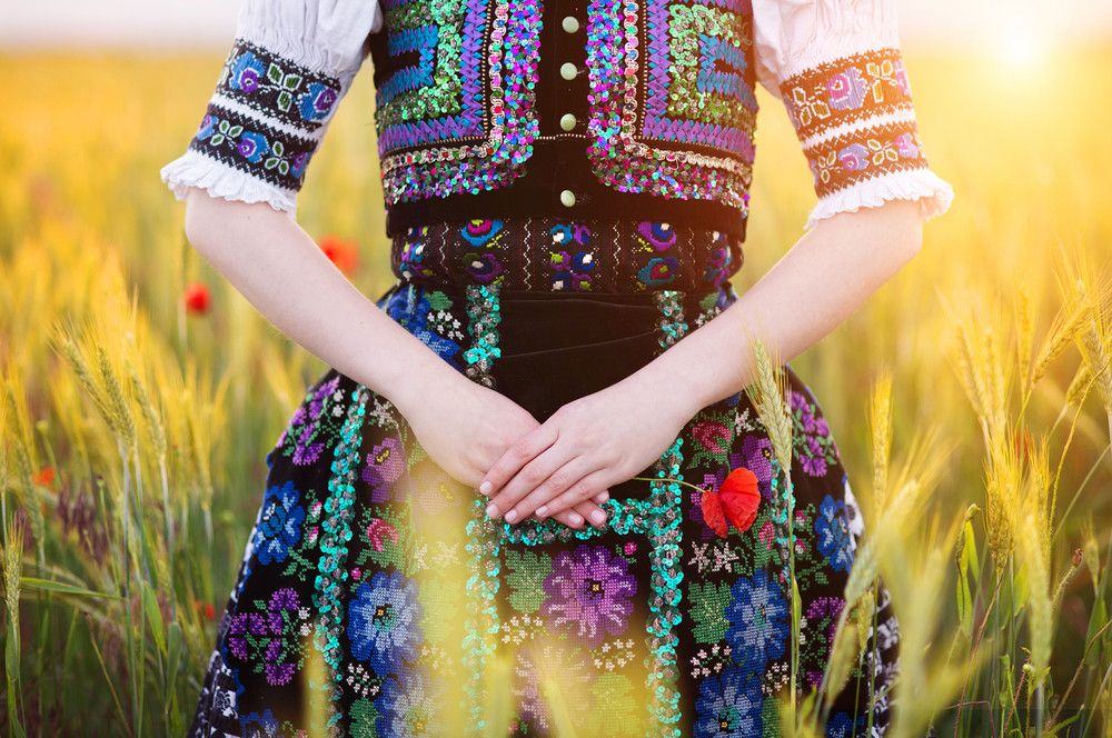 Detail of woman dress. She is wearing traditional Eastern Europe folk costumes.