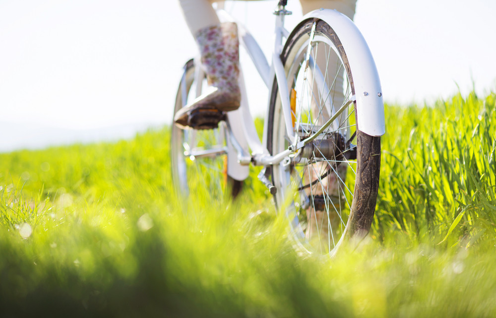 Detail of young woman's feet in boots riding on bike in green field