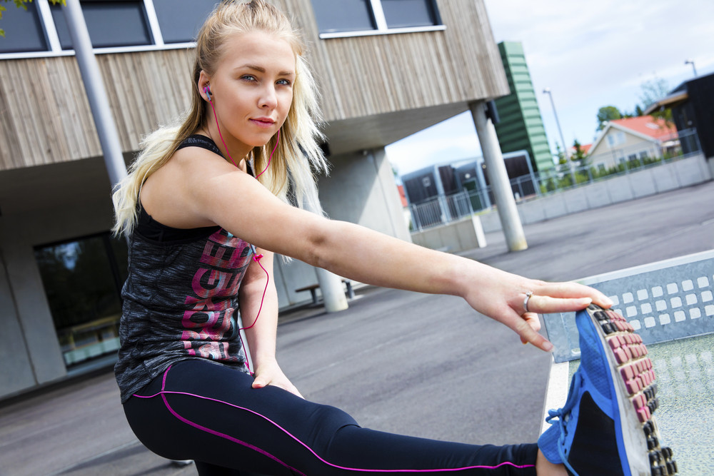 Determined Woman In Sportswear Stretching Her Leg Against Buildi