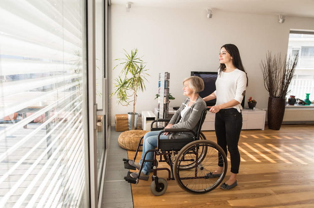 Disabled senior woman in wheelchair at home in her living room, with her young daughter caring for her, looking out the window.
