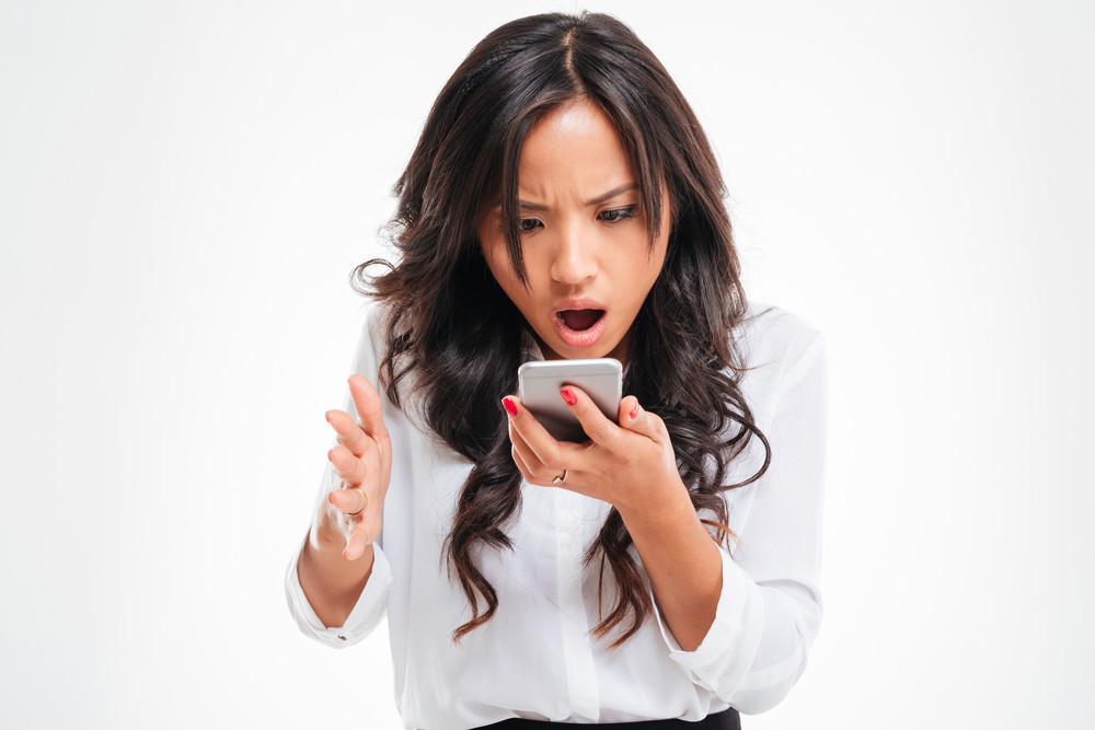 Disappointed asian businesswoman using smartphone isolated on a white background