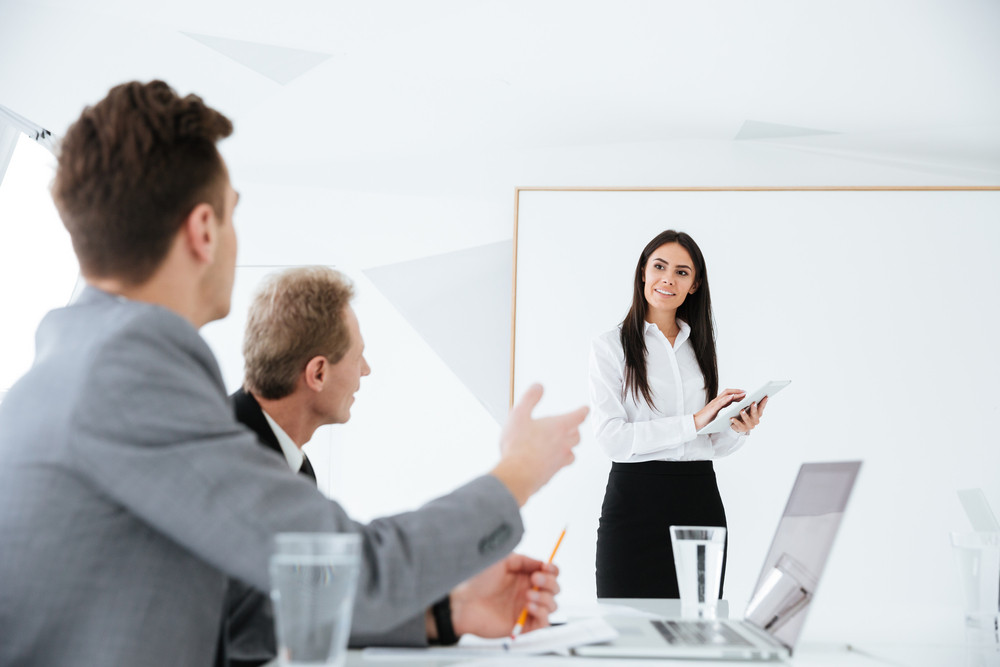Discussion of Business team on session in conference room in office. Woman standing near the board. Focus on woman