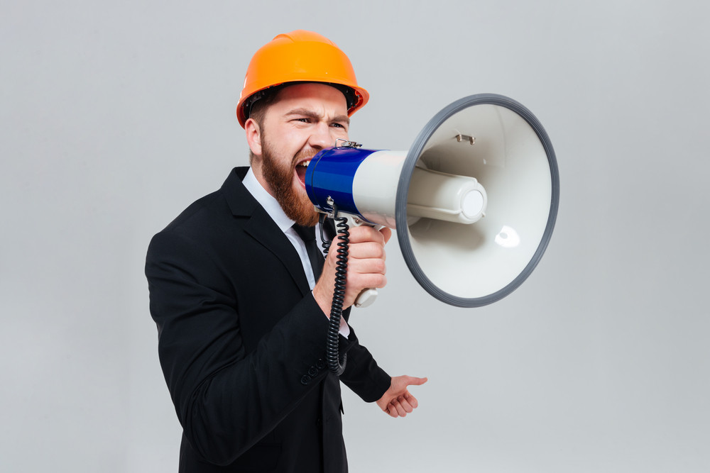Displeased bearded engineer in black suit and orange helmet shouting in megaphone and looking aside. Isolated gray background
