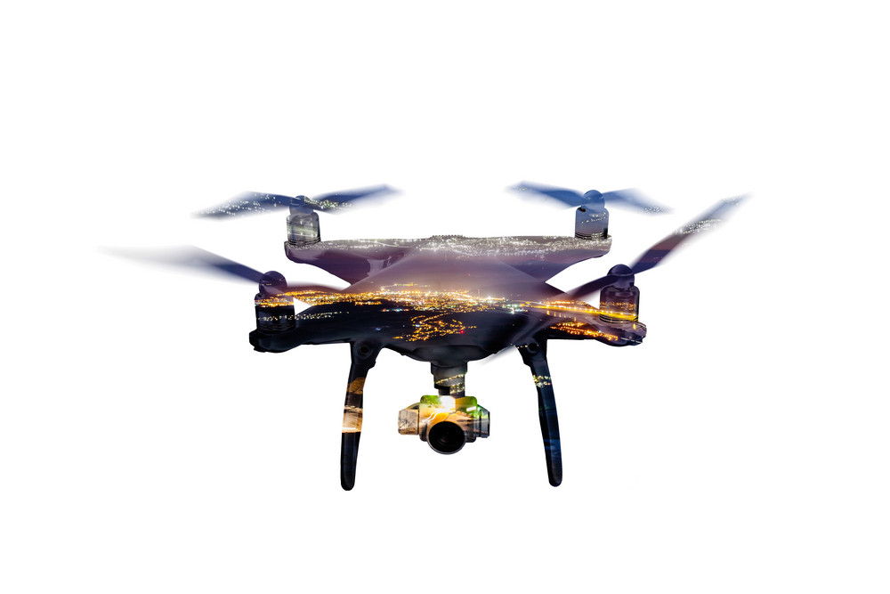 Double exposure. Close up of hovering drone taking pictures of illuminated city at night. Aerial view. Isolated.