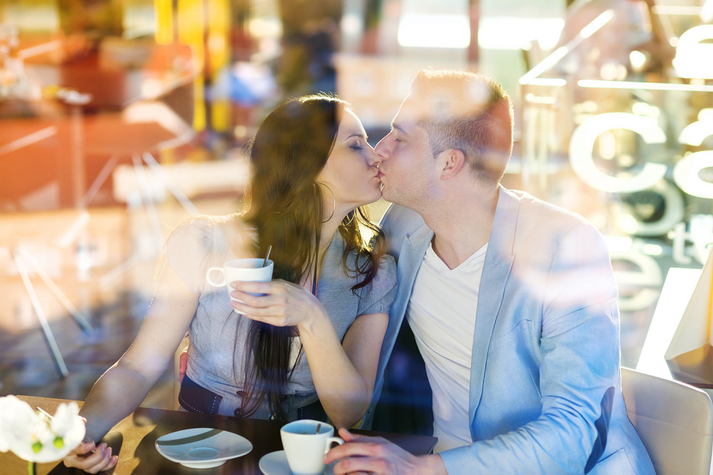 Double exposure of a beautiful young couple sitting in a cafe