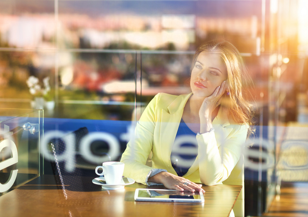 Double exposure of an attractive young woman with tablet in a cafe