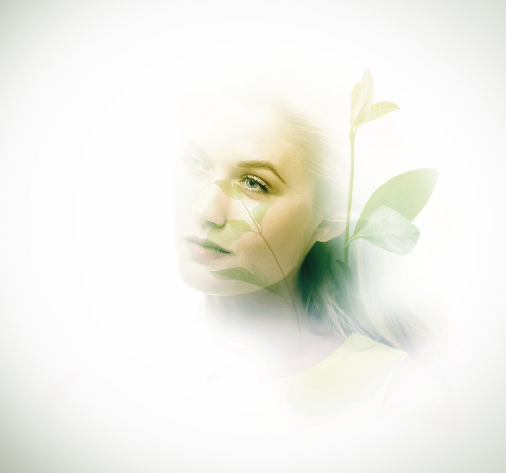 Double exposure of beautiful young woman and plants