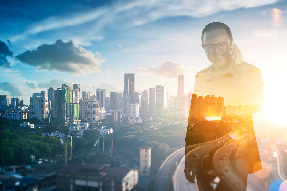 Double exposure photo, a Smiling businessman in eyeglasses talking on the phone with view of the city