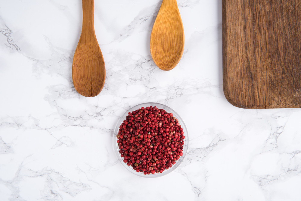 Dried pink pepperсorns in a wooden bowl with two wooden spoons and cutting surface on white marble background