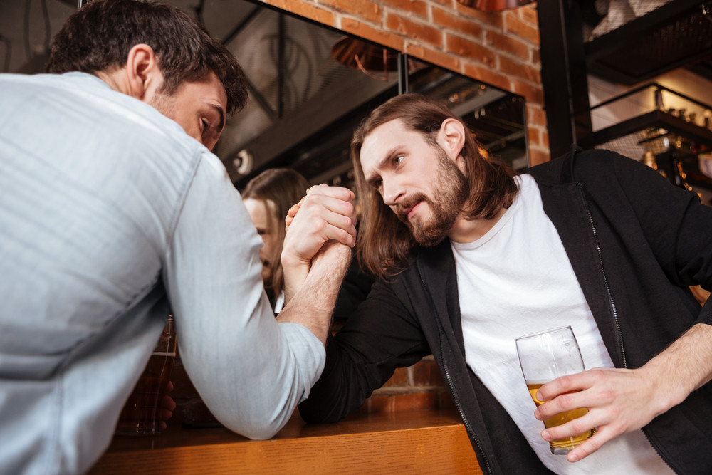 Drunk friends playing in arm wrestling near the mirror in cafe