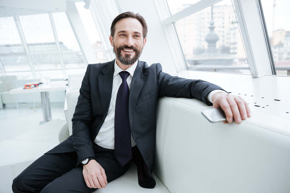 Elderly bearded business man sitting on sofa with phone near the window in office and looking at camera