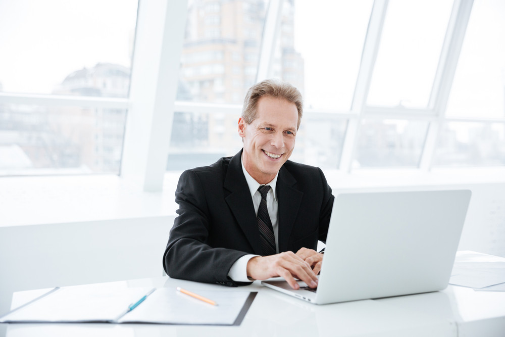 Elderly business man sitting by the table with laptop in office