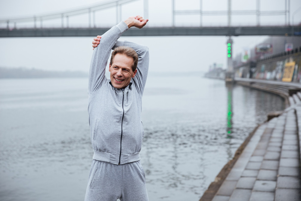 Elderly Smiling man in gray sportswear warming up near the water