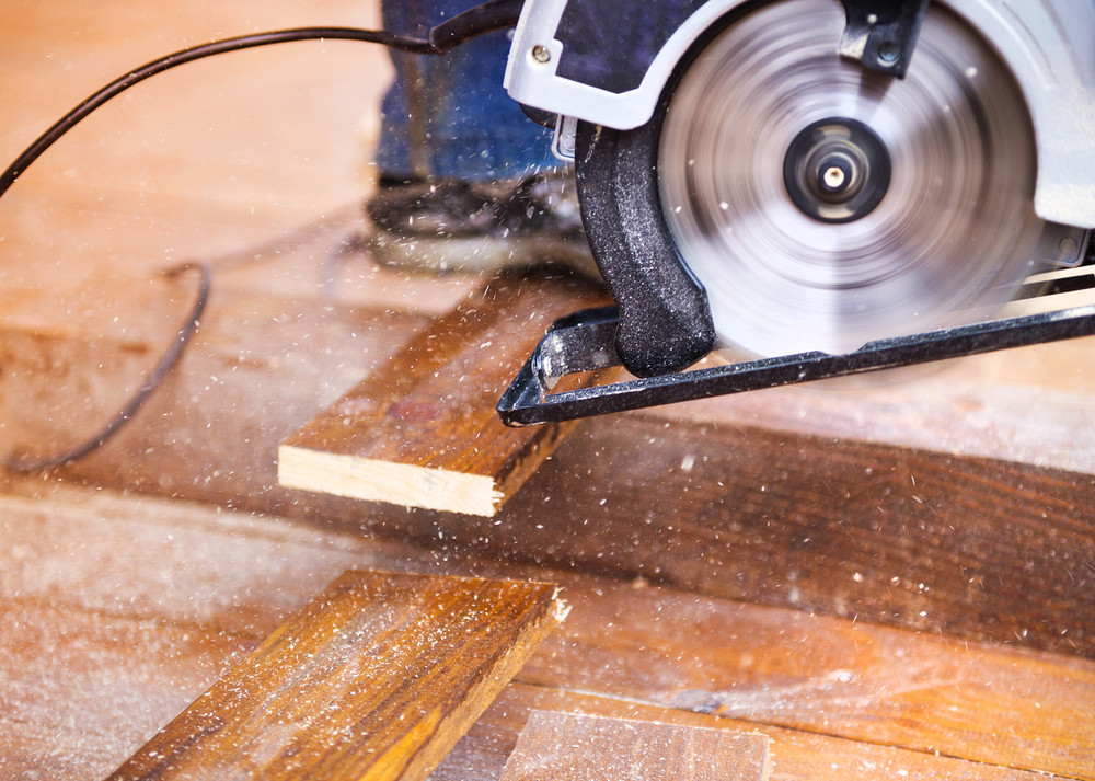 Electric grinder machine left on dusty wooden flooring with wood shavings