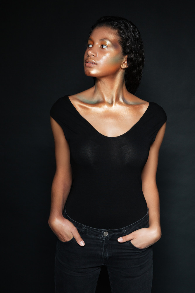 Elegant african woman in t-shirt in studio looking away. hands in pockets. isolated black background