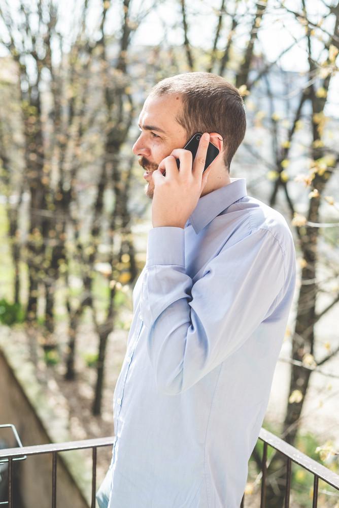 elegant business multitasking multimedia man calling with smartphone at home