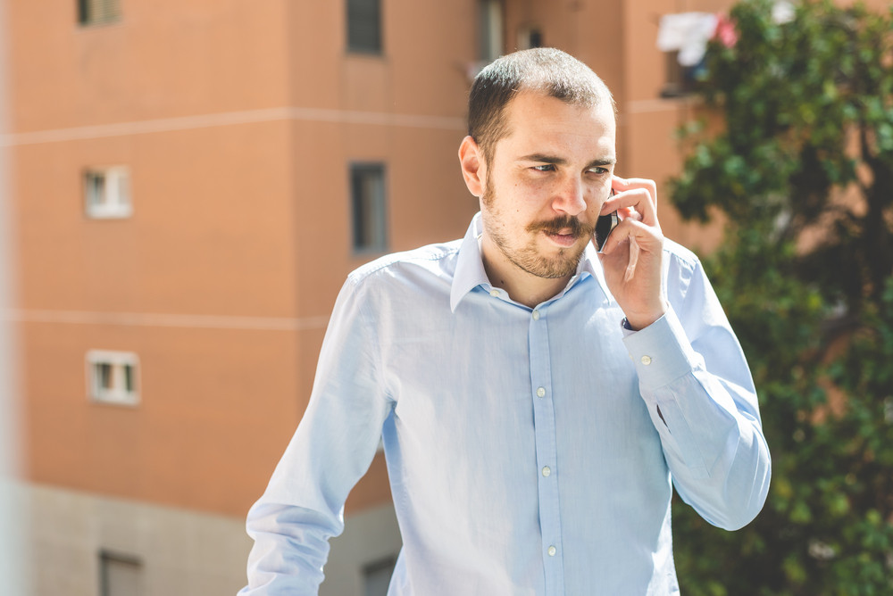 elegant business multitasking multimedia man calling with smartphone at home