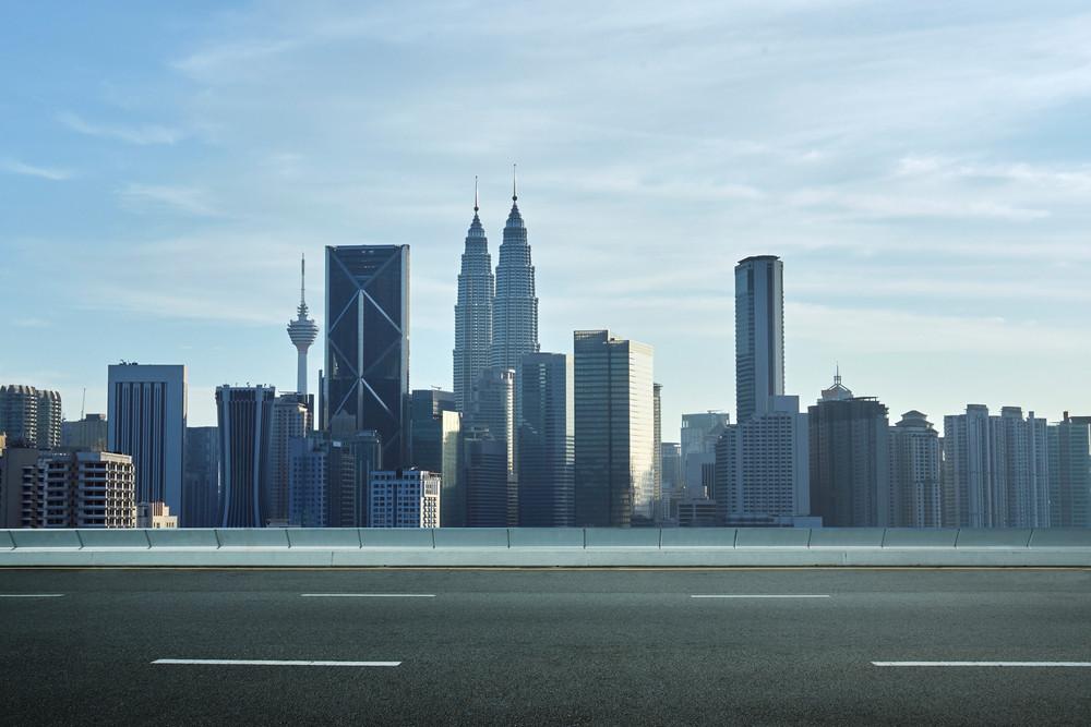 empty asphalt road and cityscape skyline , daytime scene