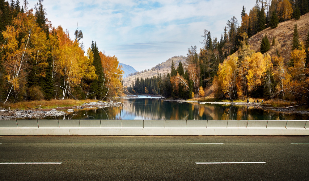 Empty asphalt road and lake mountain background .