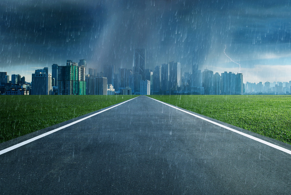 Empty asphalt road towards a city in storm