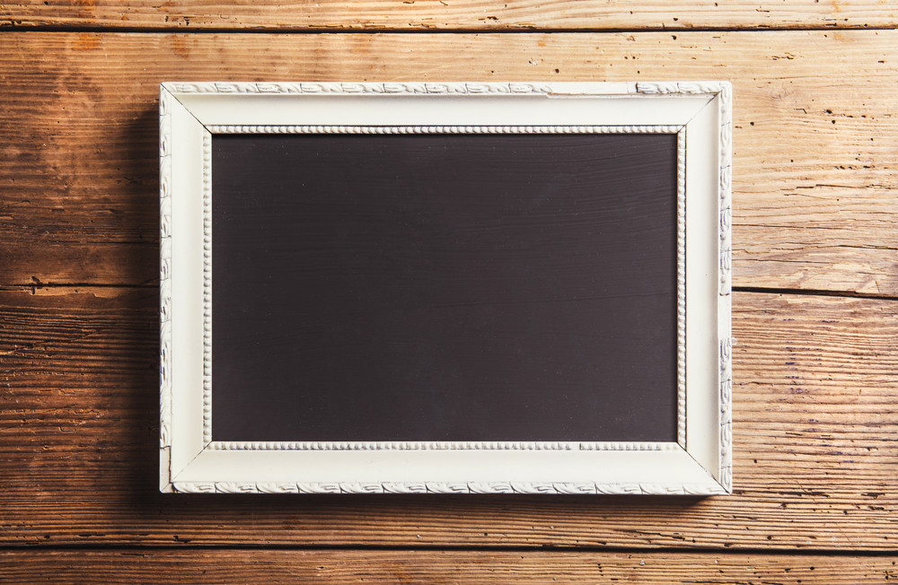 Empty picture frame. Studio shot on wooden background.