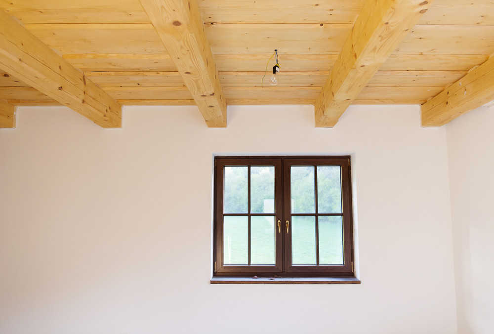 Empty unfinished room with white walls and wooden ceiling in a new constructed house