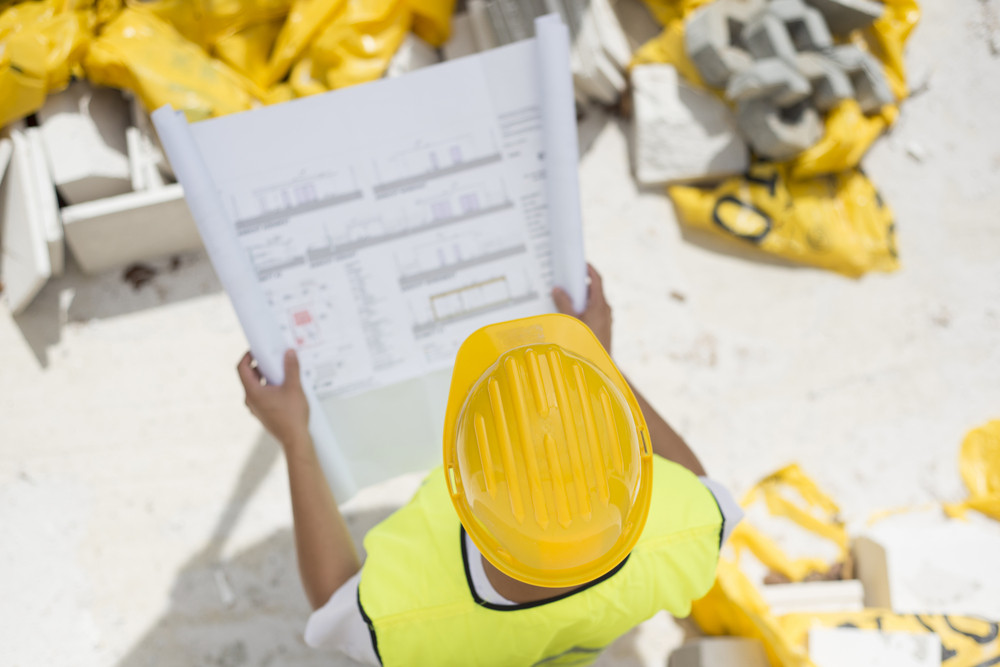 Engineer builders in safety vest with blueprint at construction site