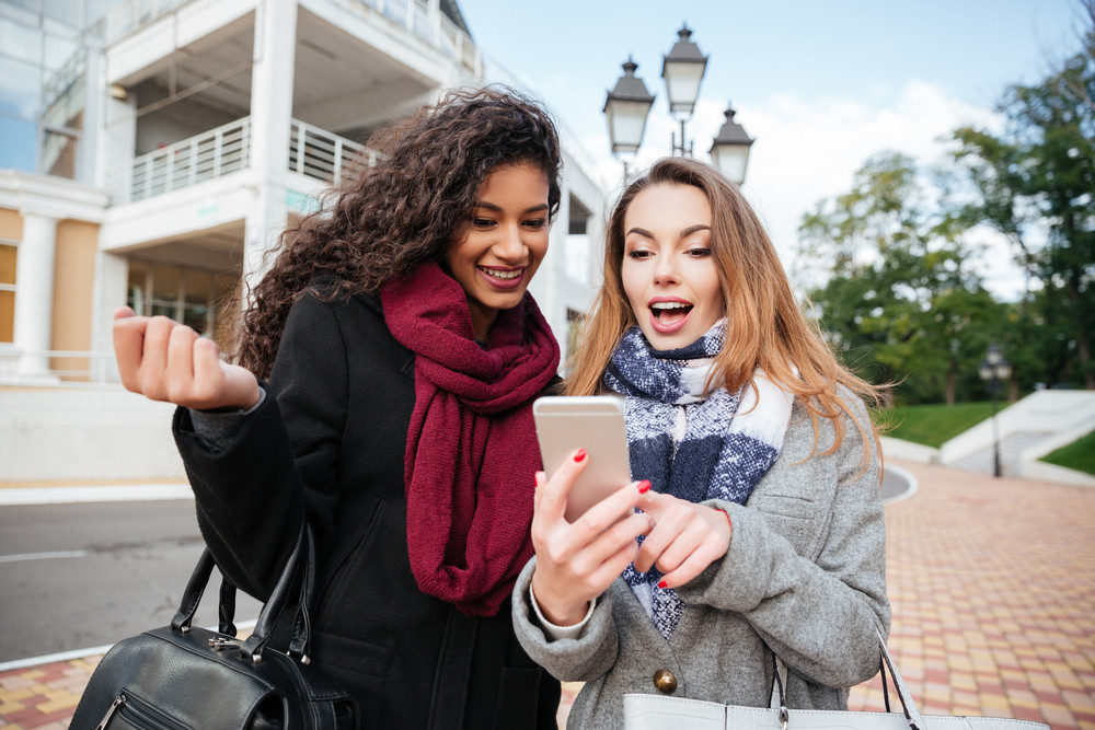 Euphoric friends watching videos on a smartphone and pointing at screen surprised. Caucasian girl wearing scarf in a cage print. African lady wearing burgundy scarf.