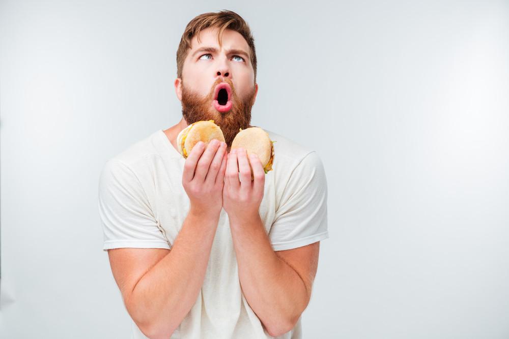Excited bearded man enjoying eating hamburgers isolated on white background