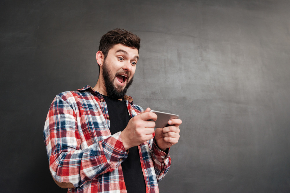 Excited man dressed in shirt in a cage playing at phone over chalkboard