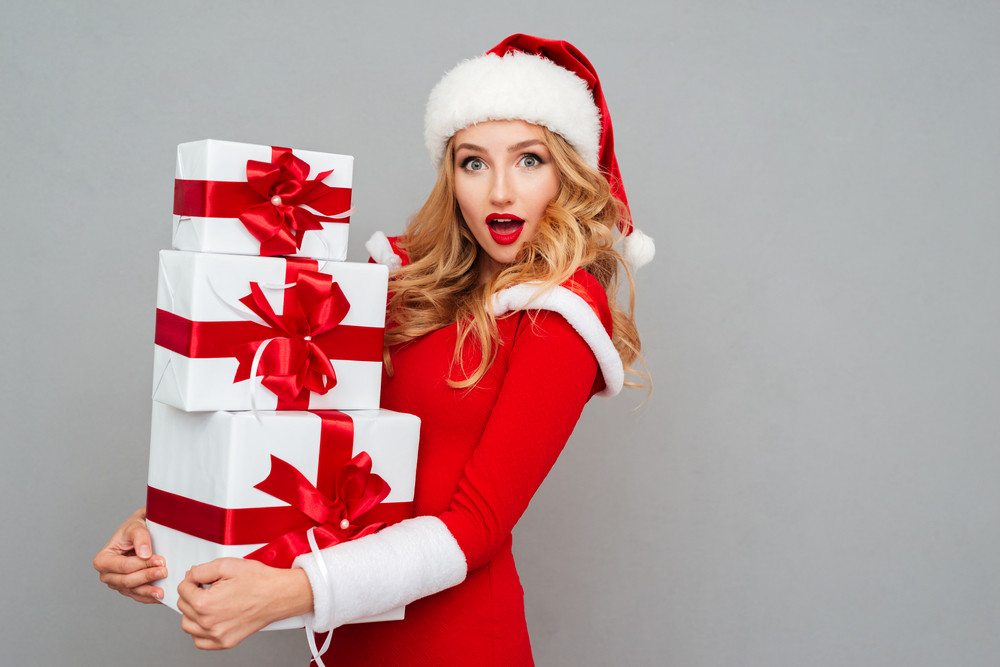 Excited surprised woman in red santa claus outfit holding stack presents isolated on the gray background