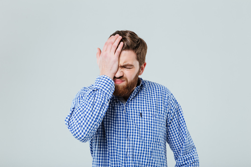 Exhausted bearded young man rubbing his eye over white background