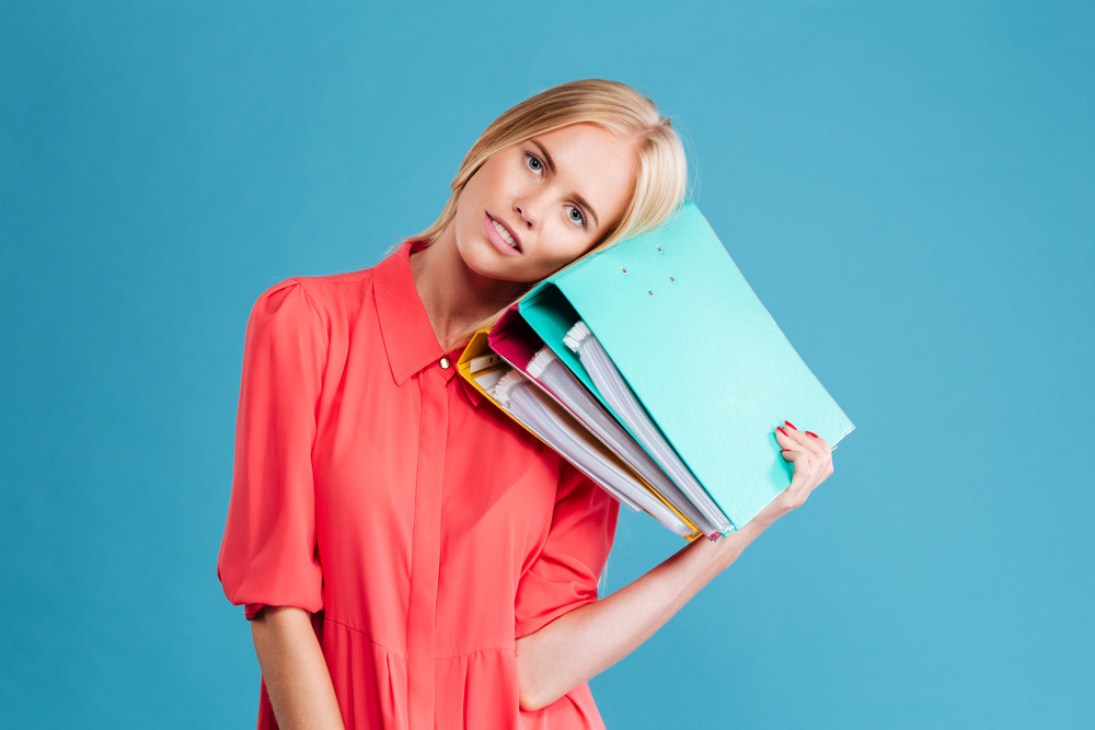 Exhausted young blonde woman with her head laying on folders over blue background