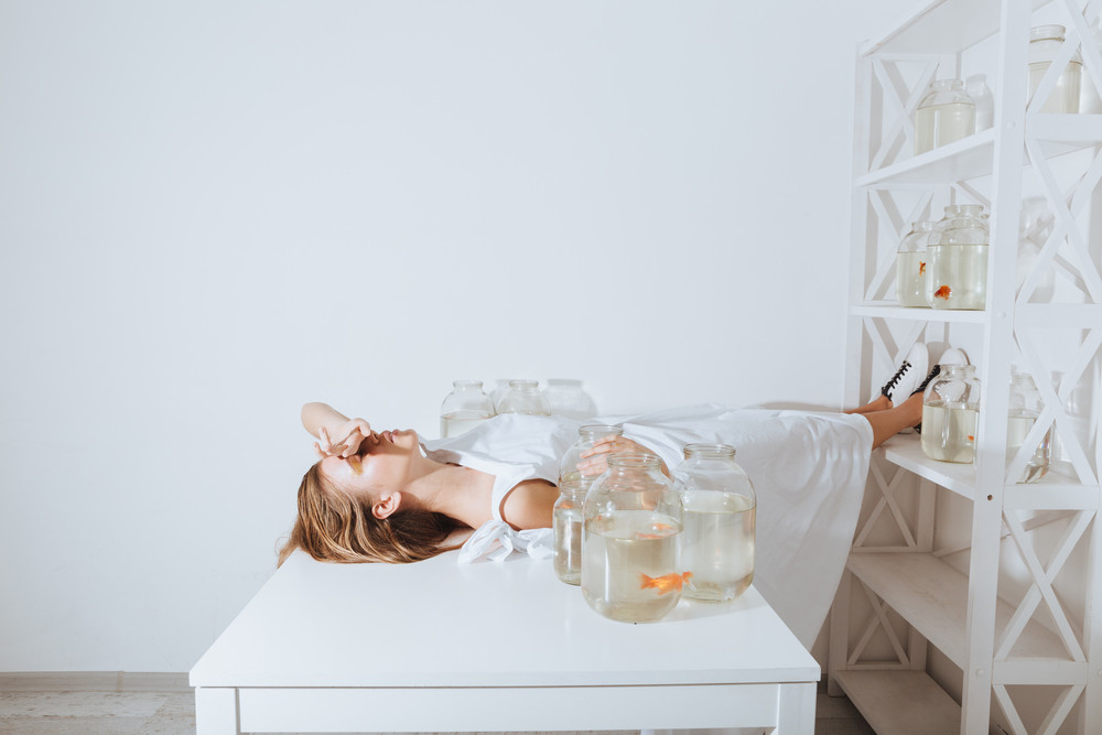Exhausted young woman lying on white table with gold fishes in jars in the room