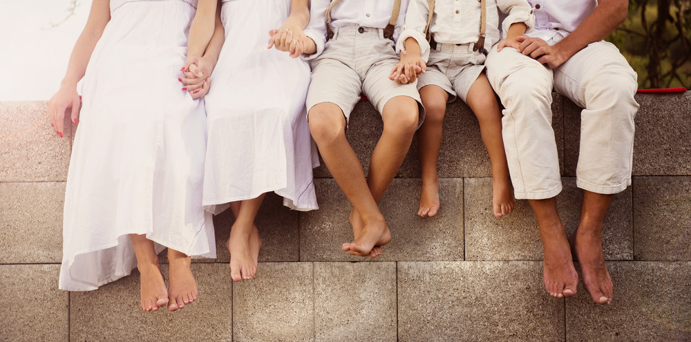 Family is sitting on the fence with the detail of bare feet