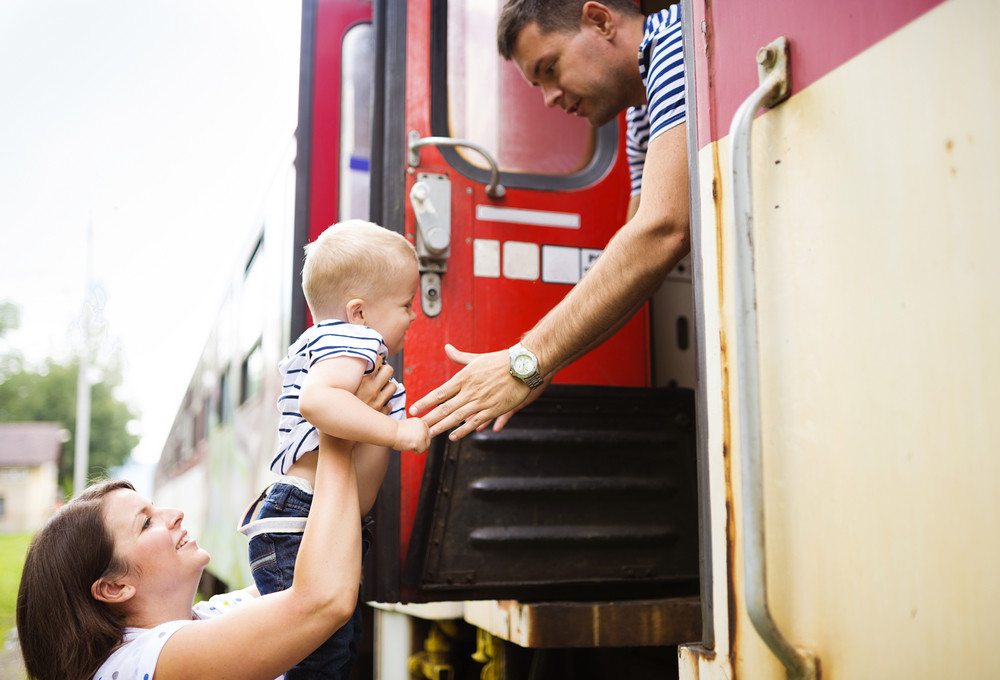 Family with a son travel entering the train.