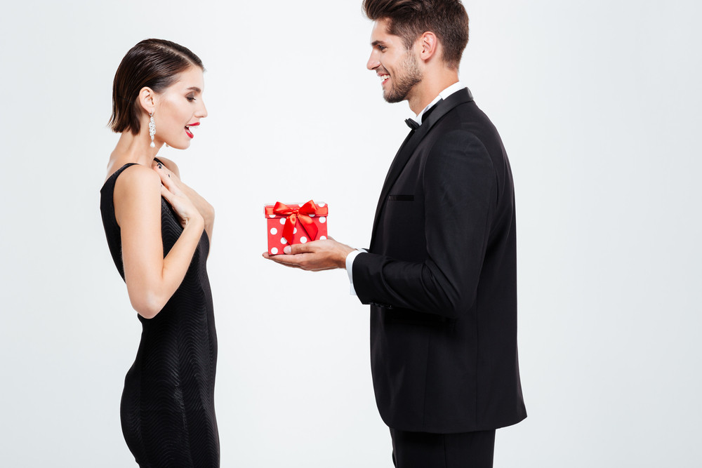 Fashion business couple with gift. woman in shock
