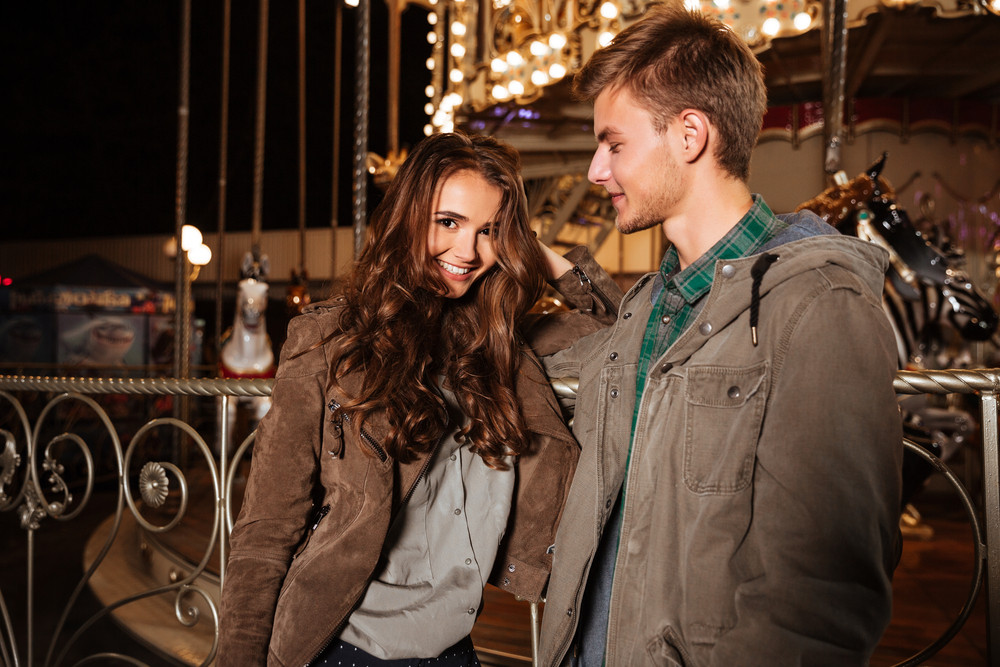 Fashion couple in amusement park. girl laughs