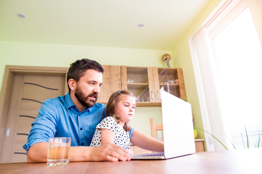 Father and daughter together, playing on laptop, sitting at the kitchen table