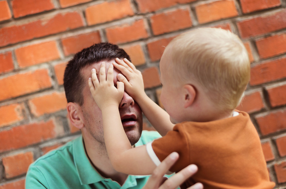 Father and son making funny faces together on a brick wall background